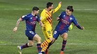 Lionel Messi dikepung pemain Huesca. Barcelona menang tipis 1-0, Senin (04/01/2021) dini hari WIB. (Pau BARRENA / AFP)
