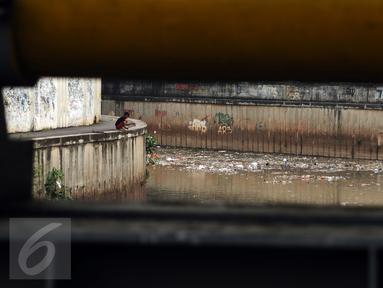 Warga memancing di Kali Krukut dekat TPU Karet Bivak Jakarta, Sabtu (5/11). Tumpukan sampah terlihat menggenang di sisi aliran Kali Krukut dan berbau. (Liputan6.com/Helmi Fithriansyah)
