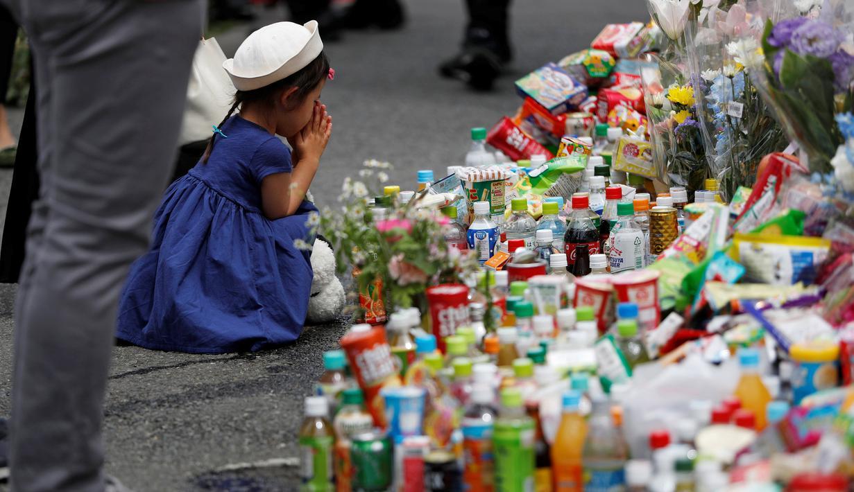 Seorang gadis berdoa usai memberikan bunga untuk korban Penikaman Massal yang terjadi di Kawasaki, Jepang (29/5/2019). Seorang siswi dan seorang pria dewasa tewas dan 17 siswi lainnya cedera akibat penikaman massal di Kota tersebut. (Reuters/Issei Kato)