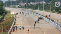 Warga berolahraga sepeda dan berlari pada waktu sore di kawasan pembangunan Tol Serpong Kunciran, Ciputat, Tangerang Selatan, Kamis (25/6/2020). Sebagian warga terlihat tidak mengindahkan protokol kesehatan seperti menggunakan masker dan physical distancing. (Liputan6.com/Fery Pradolo)