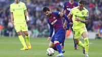 Striker Barcelona, Lionel Messi, berusaha melewati pemain Getafe, Mauro Arambarri, pada laga La Liga di Stadion Camp Nou, Sabtu (15/2/2020). Barcelona menang 2-1 atas Getafe. (AP/G.Garin)