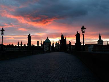 Matahari terbit di atas Jembatan Charles yang dibangun pada abad pertengahan di Praha, Republik Ceko, Kamis (8/10/2020). Infeksi virus corona COVID-19 di Ceko mencapai rekor tertinggi baru dua hari berturut-turut, melampaui 5.000 kasus dalam sehari untuk pertama kalinya. (AP Photo/Petr David Josek)