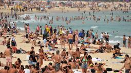 Pengunjung berjemur di pantai Bondi ketika pantai Bondi ketika suhu udara melonjak di Sydney (21/12/2019). Pemerintah negara bagian tersebut juga sudah mendeklarasikan status darurat karena situasi saat ini membahayakan warga dan wisatawan. (AFP/Farooq Khan)