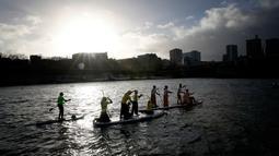 Peserta mengambil bagian dalam Nautic Paddle Race menyeberangi sungai Seine di Paris, Minggu (9/12). Sekitar 800 orang mengikuti lomba dayung sambil berdiri terbesar di dunia sejauh 11 km menyeberangi sungai Seine. (AP /Christophe Ena)