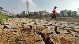 Warga beraktivitas di sekitar Kanal Banjir Barat (KBB) yang mengalami kekeringan di kawasan Tanah Abang, Jakarta, Jumat (12/7/2019). Musim kemarau yang terjadi di Ibu Kota menyebabkan debit air di KBB berkurang sehingga menimbulkan keretakan tanah di sekitarnya. (Liputan6.com/Immanuel Antonius)