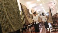 Sejumlah pengunjung melihat kain batik di Musium Bank Mandiri, Jakarta, Rabu (25/10). Pameran batik 100 kain negeri tersebut merupakan karya desainer Oscar Lawalata. (Liputan6.com/Angga Yuniar)