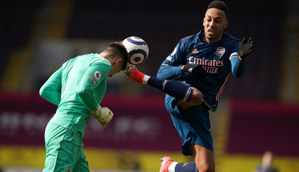 Kiper Burnley, Nick Pope menanduk bola dari ancaman striker Arsenal, Pierre-Emerick Aubameyang dalam laga lanjutan Liga Inggris 2020/21 di Turf Moor, Burnley, Sabtu (6/3/2021). Burnley bermain imbang 1-1 dengan Arsenal. (AFP/Jon Super/Pool)