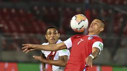 Penyerang Chile, Alexis Sanchez dan gelandang Peru, Yoshimar Yotún berebut bola dalam laga Kualifikasi Piala Dunia 2022 zona Conmebol di Estadio Nacional, Santiago, Jumat (13/11/2020). Chile mengalahkan Peru 2-0 berkat gol yang diborong Arturo Vidal. (Martin Bernetti, Pool via AP)