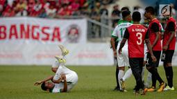 Pemain timnas Indonesia Evan Dimas terjatuh saat keributan dalam laga penyisihan grup B SEA Games XXIX Kuala Lumpur di Stadion Majlis Perbandaran Selayang, Malaysia, Minggu (20/8). (Liputan6.com/Faizal Fanani)