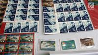 Barang bukti tindak pidana pemalsuan atau pencurian data elektronik (skimming) di Polda Metro Jaya, Jakarta, Senin (19/3). Polisi menyita 196 kartu ATM, dua alat deep skimmer, laptop, paspor, dan uang tunai Rp 50 juta. (Liputan6.com/Arya Manggala)
