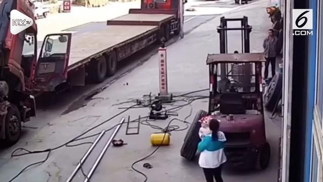 Rekeman video CCTV yang memperlihatkan sebuah ban mobil meledak dan mencederai seorang Ibu dan anak hingga terpental ke udara.