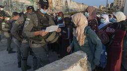 Wanita Palestina menunggu untuk menyeberangi pos pemeriksaan Qalandia antara kota Ramallah Tepi Barat dan Yerusalem, untuk menghadiri sholat Jumat pertama di masjid al-Aqsa, selama bulan suci Ramadhan, Jumat (16/4/2021).  (AP Photo/Nasser Nasser)