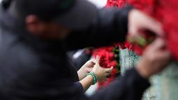 Penduduk setempat menyelesaikan pembuatan piramida Cochasqui dari bunga mawar yang diklaim terbesar dunia di Tabacundo, Ekuador, 20 Juli 2018. Sebanyak 500 ribu mawar dari 150 petani bunga digunakan untuk membangun piramida ini. (AP/Dolores Ochoa)