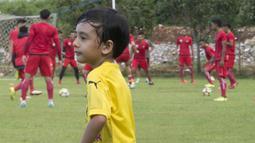Anak dari Stefano Teco, yang bernama Romario, bermain saat latihan Persija Jakarta di Lapangan Sutasoma, Jakarta, Minggu (25/2/2018). Ketika ayahnya bekerja sang anak asyik bermain sepak bola. (Bola.com/Aspirilla Dwi Adha)