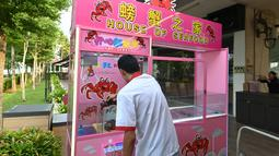 Pekerja memasukkan kepiting ke dalam mesin capit di sebuah restoran makanan laut di Singapura, 23 Oktober 2019. Rekaman video yang diunggah ke media sosial oleh pengelola restoran untuk mempromosikan mesin capit tersebut malah memunculkan kritikan deras. (Roslan RAHMAN / AFP)