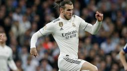 Gelandang Real Madrid, Gareth Bale berusaha melewati gelandang Barcelona, Gerard Pique selama pertandingan lanjutan La Liga Spanyol di stadion Santiago Bernabeu, Madrid (2/3). Barcelona menang tipis atas Real Madrid 1-0. (AP Photo/Andrea Comas)