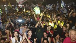 Warga Israel merayakan pelantikan pemerintahan baru di Tel Aviv, Israel, Minggu, 13 Juni 2021. Naftali Bennett, mantan sekutu Benjamin Netanyahu menjadi perdana menteri baru Israel. (AP Photo/Oded Balilty)