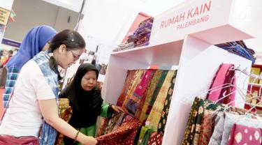 Pengunjung melihat produk Rumah Kain Palembang di booth YDBA pada Jakarta Fair Kemayoran 2019 di JIExpo Kemayoran, Jakarta, Rabu (19/6/2019). YDBA mengikutsertakan 40 UMKM mulai dari produk fashion, aksesoris, kerajinan, alat rumah tangga hingga makanan hingga 30 Juni 2019. (Liputan6.com/HO/Eko)