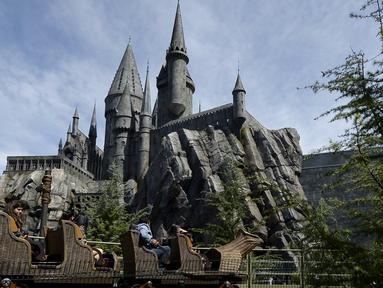 """Pengunjung menaiki rollercoaster di depan sekolah Hogwarts saat soft opening dan tur media taman bermain bertemakan """"The Wizarding World of Harry Potter"""" di Universal Studios Hollywood, Los Angeles, California, 22 Maret 2016. (REUTERS/Kevork Djansezian)"""