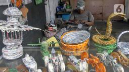 Perajin menyelesaikan pembuatan kerajinan tangan berbahan dasar koran bekas di bengkel Workshop kawasan Kemandoran 8 Jakarta Selatan, Senin (10/2/2020). Berbagai kerajinan berwujud keranjang, lampu belajar, miniatur pesawat berbahan koran bekas dibuat ditempat ini. (merdeka.com/Arie Basuki)