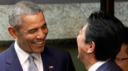 Presiden AS ke-44 Barack Obama dan PM Jepang, Shinzo Abe tertawa di depan salah satu restoran sushi di kawasan Ginza, Tokyo, Jepang, (25/3). (AP Photo / Shizuo Kambayashi, Pool)