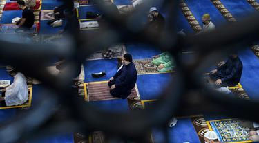 Umat muslim menjaga jarak saat salat Jumat usai pencabutan pembatasan Covid-19 di Masjid Al-Istighfar, Singapura, Jumat (26/6/2020). Masjid-masjid di Singapura telah diizinkan menggelar salat berjamaah, seiring memasuki pekan kedua dari Tahap Dua pembukaan kembali di negara itu. (Roslan RAHMAN/AFP)
