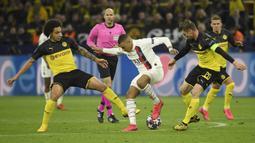 Striker Paris Saint-Germain, Kylian Mbappe, berebut bola dengan pemain Borussia Dortmund pada leg pertama 16 besar Liga Champions di Signal Iduna Park, Dortmund, Rabu (19/2) dini hari WIB. Dortmund menang 2-1 atas PSG. (AFP/Ina Fassbender)