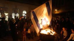 Seorang Yahudi ultra ortodoks antizionis membakar bendera Israel di Yerusalem ultra-Ortodoks Mea Shearim, Rabu (2/5). Upacara ini menandai peringatan kematian Rabbi Talmudic Rabbi Shimon Bar Yochai sekitar 1.900 tahun lalu. (MENAHEM KAHANA / AFP)