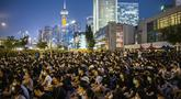 Sejumlah mahasiswa duduk menghadiri rapat umum di Edinburgh Place di Hong Kong (22/8/2019). Pemimpin mahasiswa Hong Kong memboikot perkuliahan selama dua minggu. (AFP Photo/Anthony Wallace)