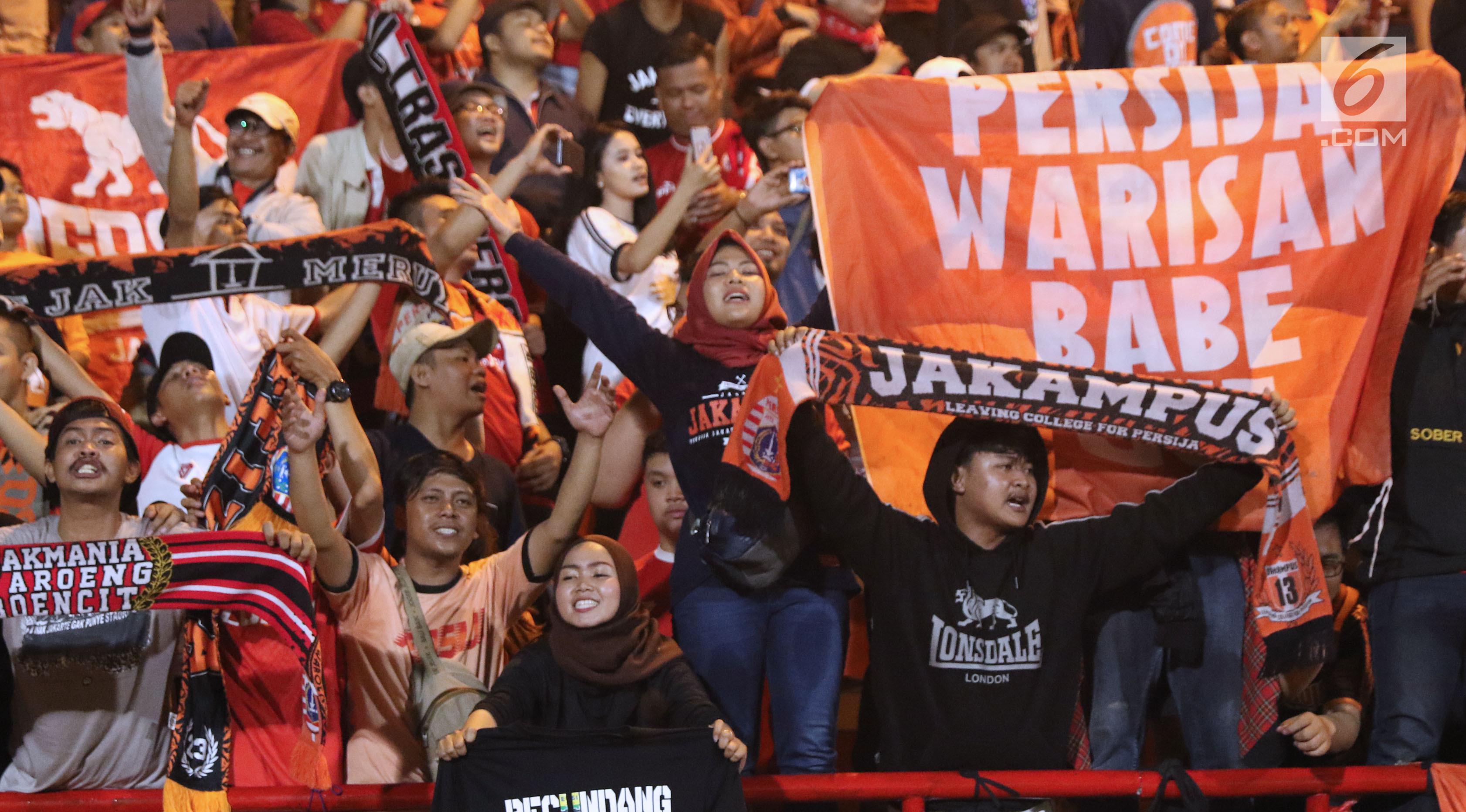 Suporter Persija bersorak merayakan kemenangan atas Persib pada lanjutan Go-Jek Liga 1 Indonesia 2018 bersama Bukalapak di Lapangan PTIK, Jakarta, Sabtu (30/6). (Liputan6.com/Helmi Fithriansyah)