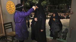 Jemaah diperiksa suhu tubuhnya saat akan memburu malam lailatul qadar di Masjid Universitas Teheran, Laylat al-Qadr, Iran, Selasa (12/5/2020). Iran mengizinkan masjid dibuka kembali, namun dengan memperhatikan prosedur kesehatan dan sosial untuk mencegah penyebaran COVID-19. (AP Photo/Vahid Salemi)