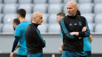 Pelatih Real Madrid, Zinedine Zidane (kanan) mengawasi sesi latihan di Allianz Arena, Munich, (24/4/2018). Real Madrid akan melawan tuan rumah Bayern Munchen pada semifinal Liga Champions. (AFP/Javier Soriano)