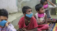 Anak-anak yang mengenakan masker sebagai pencegahan virus corona mengikuti kelas online di sebuah perkampungan kumuh di pinggiran Jammu, India, Senin, 14 Juni 2021. (AP Photo/Channi Anand)