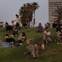 Orang-orang tanpa masker menyaksikan matahari terbenam, di Tel Aviv, Minggu (18/4/2021). Israel mencabut aturan wajib masker di ruang publik luar ruangan dan membuka kembali sekolah sepenuhnya dalam upaya menuju normalisasi setelah kampanye vaksinasi Covid-19 berjalan sukses. (AP Photo/Oded Balilty)
