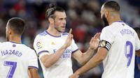 Los Blancos membuka kedudukan terlebih dahulu lewat gol cepat Gareth Bale (kiri) ketika babak pertama baru berjalan lima menit. Bale sukses menuntaskan umpan Benzema meski dirinya dikawal oleh dua pemain. Papan skor berubah menjadi 1-0 atas keunggulan Real Madrid. (Foto: AP/Alberto Saiz)