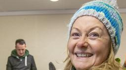 Petugas pendidikan sekolah untuk Rehabilitasi Satwa Liar Irlandia, Aoife McPartlin memegang kambing liar Irlandia berusia dua minggu yang ditemukan di lereng gunung, di belakang Tara na Ri Pub, yang ditutup karena lockdown Covid-19 di County Meath di Dublin pada 18 Februari 2021. (PAUL FAITH/AFP)