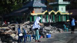 Seorang anak yang terkena dampak gempa meminta sumbangan pada pengguna jalan yang melintas di Donggala, Sulawesi Tengah, Jumat (5/10). Akibat terlambatnya pasokan bantuan, mereka terpaksa meminta sumbangan hingga turun ke jalan. (AFP PHOTO / Jewel SAMAD)
