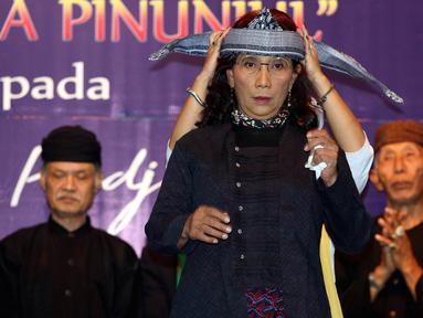 Menteri Kelautan dan Perikanan Susi Pudjiastuti  dipakaikan totopong saat pertemuan dengan Masyarakat Adat Jawa Barat di Jakarta, Rabu (19/3). Dalam acara itu, Susi menerima gelar kehormatan dari masyarakat adat Jawa Barat. (Liputan6.com/Johan Tallo)