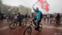 Pendukung oposisi Belarusia mengendarai sepeda dan mengibarkan bendera nasional Belarusia selama unjuk rasa di depan gedung pemerintah di Lapangan Independen di Minsk, Belarusia pada 19 Agustus 2020. (AP Photo / Dmitri Lovetsky)