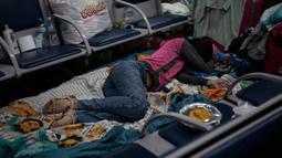 Imigran Kolombia yang telantar tidur di Bandara Internasional Guarulhos, di Guarulhos, dekat Sao Paulo, Selasa (26/5/2020). Ratusan orang yang menunggu bantuan untuk kembali ke negara mereka itu hidup dari sumbangan, tidur di lantai dan bangku serta mandi di toilet bandara. (Miguel SCHINCARIOL/AFP)