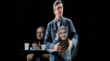 Sepasang tamu duduk sambil mengamati hologram tiga dimensi (3D) calon presiden indepeden Prancis dari kelompok sayap kiri, Jean-Luc Melenchon, yang sedang berpidato di lokasi kampanye di Saint-Denis, dekat Paris, Minggu (5/2). (AP Photo/Kamil Zihnioglu)