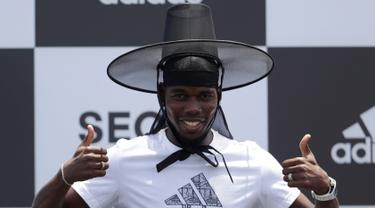 Gelandang Manchester United, Paul Pogba berpose mengenakan topi tradisional Korea Selatan saat jumpa pers di Seoul, Korea Selatan, Kamis (13/6/2019). Paul Pogba berada di Seoul sebagai bagian dari tur Asia-nya. (AP Photo/Lee Jin-man)