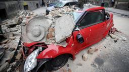 Kondisi sebuah mobil yang hancur tertimpa reruntuhan bangunan setelah guncangan gempa di pusat kota Zagreb, Korasia (22/3/2020). Setelah gempa hari Minggu, wali kota Zagreb mendesak orang-orang untuk kembali ke rumah karena khawatir tentang Virus Corona COVID-19. (AFP/Damir Sencar)