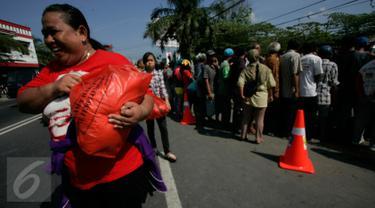 Seorang warga membawa sembako yang dibagikan oleh Presiden Joko Widodo atau Jokowi di halaman Gedung Graha Saba, Solo, Jawa Tengah, Jumat (8/7). Keluarga Jokowi membagikan 2.200 paket sembako kepada warga Solo. (Liputan6.com/Boy Harjanto)