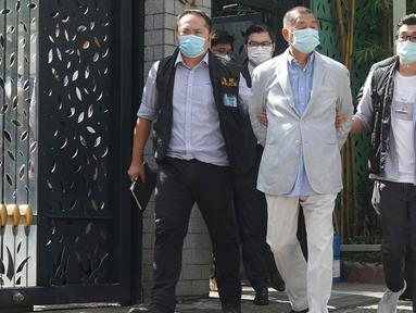 Taipan media Hong Kong, Jimmy Lai (tengah) ditangkap oleh petugas polisi di rumahnya di Hong Kong, Senin (10/8/2020). Pendiri surat kabar lokal Apple Daily itu ditangkap atas tuduhan pelanggaran Undang-Undang Keamanan Nasional Hong Kong karena dianggap berkolusi dengan kekuatan asing. (AP Photo)