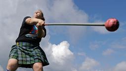 Meagan McKee melempar palu saat mengikuti Grandfather Mountain Highland Games ke-64 di MacRae Meadows, Linville, North Carolina, AS, Jumat (12/7/2019). Kejuaraan ini digelar untuk merayakan sejarah dan budaya Skotlandia. (AP Photo/Chuck Burton)