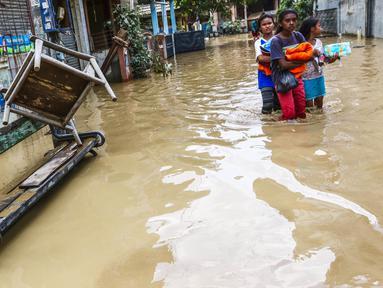 Sejumlah anak perempuan melintasi banjir yang masih merendam komplek Pondok Gede Permai, Jatiasih, Bekasi, Jumat (22/4). Sejak banjir menerjang perumahan tersebut hanya ada sekitar 50 warga yang mau dievakuasi. (Liputan6.com/Fery Pradolo)
