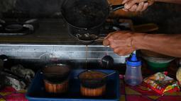 Seorang pria membuat kopi Kawa Daun di sebuah kafe tradisional, Tabek, Sumbar (29/11). Kopi Kawa Daun adalah minuman kuno yang berasal dari masa kolonial ketika sedikit penduduk setempat yang mampu membeli kopi yang diekstrak. (AFP Photo/Adek Berry)