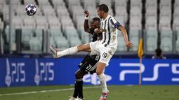 Bek Juventus, Leonardo Bonucci berebut bola dengan penyerang Lyon, Karl Toko Ekambi pada leg kedua babak 16 besar Liga Champions di Allianz stadium, Turin, Italia (7/8/2020). Juventus menang 2-1 atas Lyon, namun tersingkir dari Liga Champions setelah aggregat skor 2-2. (AP Photo/Antonio Calanni)