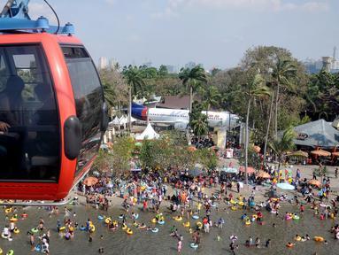 Pengunjung menggunakan wahana Gondola untuk menikmati area wisata Ancol, Jakarta, Sabtu (18/7/2015). Wisata pantai Ancol masih menjadi pilihan favorit warga Jakarta untuk mengisi libur lebaran kedua ini bersama keluarga. (Liputan6.com/JohanTallo)